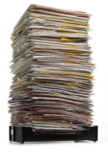 high stack of papers in inbox