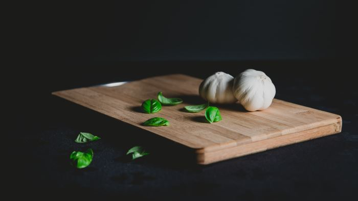 clean bamboo cutting board with garlic heads and basil