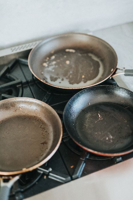 3 dirty Hard Anodized pans on stove