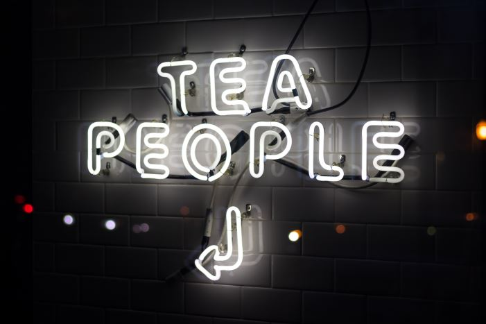 neon sign saying tea people