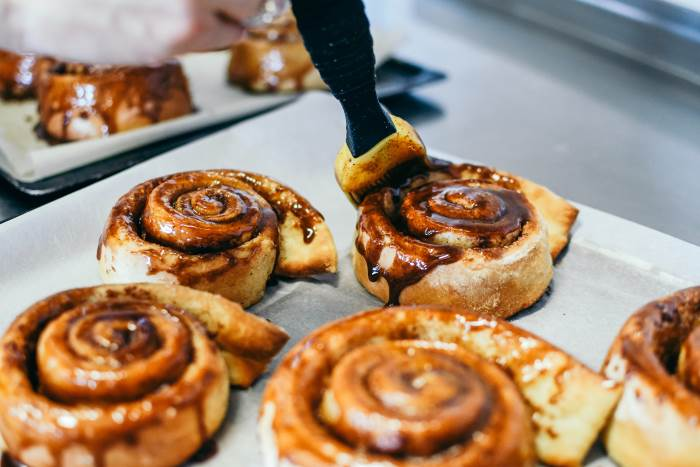 covering cinnamon rolls with glaze