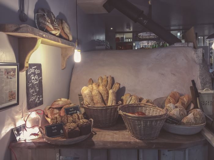 bakery counter with several kinds of artisan breads